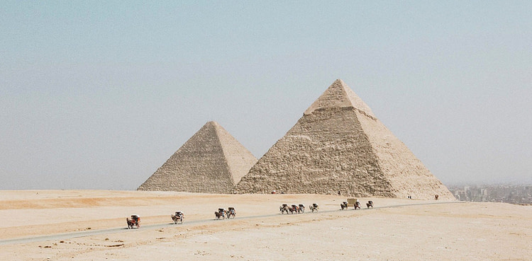 people travelling towards two pyramids