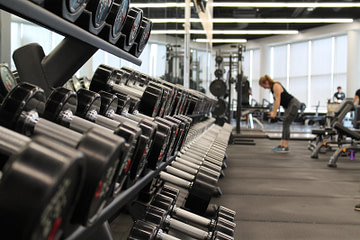 woman standing surrounded by exercise equipment
